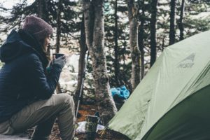 Woman sat outside a tent in the woods
