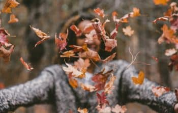 Person throwing autumn leaves