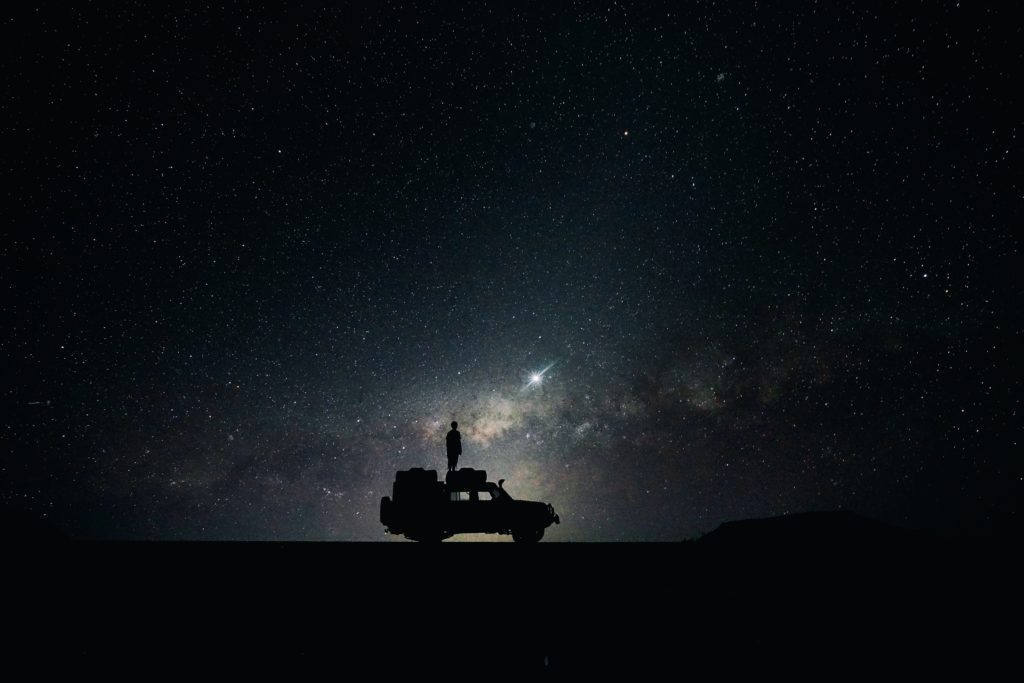 Man stood in on a car under the night sky